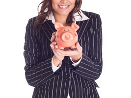 Geschäftsfrau mit Sparschwein lächelt